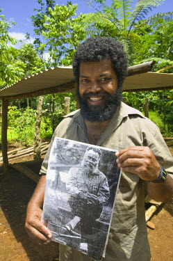 VA01063 Vanuatu, Espiritu Santo Island Fanafo, Fanafo Kastom (traditional) village- Yankee Stevens, son of Vanuatu Independence activist Jimmy Stevens with a portrait of his father