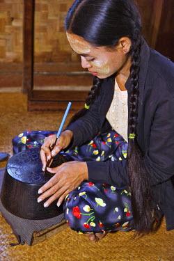MYA1098 Myanmar. Burma. Bagan. A Burmese woman engraving a lacquer bowl at a lacquer workshop in Bagan.