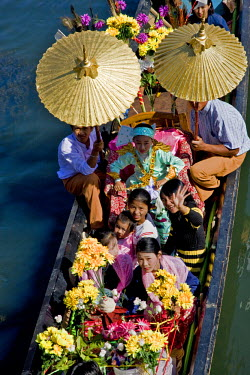 MYA1175 Myanmar, Burma, Lake Inle. A young novitiate shaded with golden umbrellas travels by boat during a ceremony in which the boy is inducted as a novice Buddhist monk.