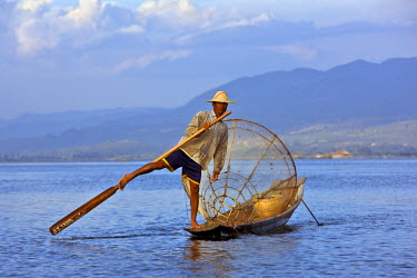 Myanmar, Burma, Lake Inle. An Intha fisherman with a traditional fish trap uses an unusual leg-rowing technique to propel his flat-bottomed boat across the lake while standing.