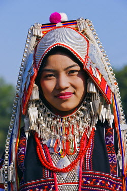 Myanmar, Burma, Kengtung. An Akha woman wearing traditional costume with a headdress of silver and beads.