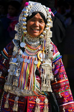 Myanmar, Burma, Kengtung. An Akha woman wearing traditional costume with a silver headdress and necklace embellished with glass beads.