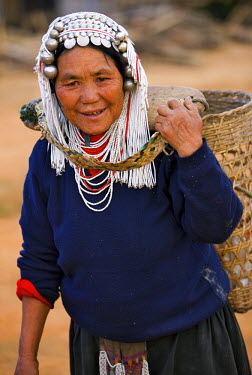 Myanmar, Burma, Namu-op. An Akha woman wearing a headdress of silver and glass beads, carries a large bamboo basket supported at the back of her neck by a yoke.