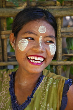 MYA1335 Myanmar, Burma, Kaladan River. A Rakhine woman with Thanakha, a popular local sun cream favoured by women and girls as a skin or anti-wrinkle cream.