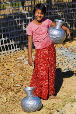 MYA1366 Myanmar, Burma, Mrauk U. A Rakhine girl with aluminium water containers at Mrauk U.  These containers are imported from India or Bangladesh.