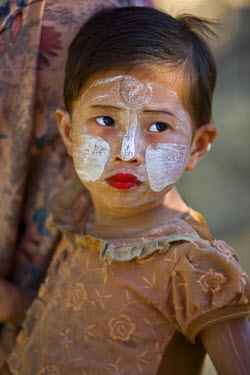 MYA1368 Myanmar, Burma, Mrauk U. A young That girl at Mrauk U with her face decorated with Thanakha, a popular local sun cream and skin lotion.