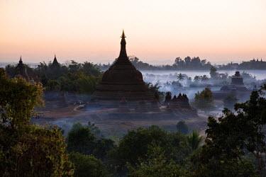 MYA1373 Myanmar, Burma, Mrauk U. Smoke swirls around the historic bell-shaped temples of Mrauk U at dusk. They were built in the Rakhine style between the 15th and 17th centuries.