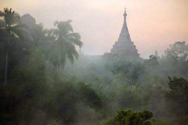 MYA1374 Myanmar, Burma, Mrauk U. Early morning mist shrouds an historic temple of Mrauk U built in the Rakhine style between the 15th and 17th centuries.