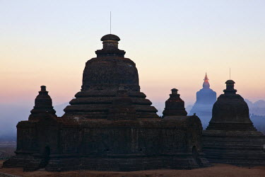 MYA1375 Myanmar, Burma, Mrauk U. Early morning mist swirls around the historic bell-shaped temples of Mrauk U which were built in the Rakhine style between the 15th and 17th centuries.