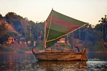 MYA1394 A large wooden boat of Rakhine design sails up the Lay Myo River in fading evening light.