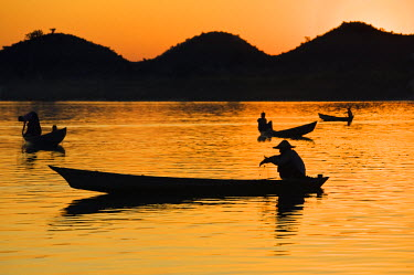 MYA1395 Fishermen bathed in the golden hues of the setting sun as they fish from their little boats on the Lay Myo River.