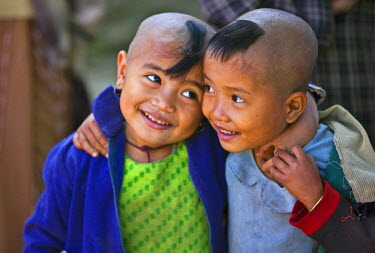 MYA1402 Myanmar, Burma, Rakhine State,Gyi Dawma village. Two young friends at Gyi Dawma village. The small tufts of hair on their shaven heads are believed to protect them.