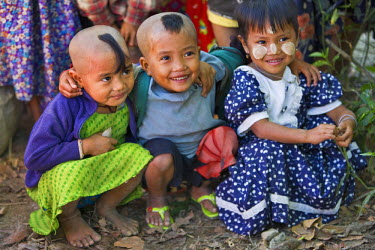 MYA1404 Myanmar, Burma, Rakhine State, Gyi Dawma. Three young friends at Gyi Dawma village. The small tufts of hair on the shaven heads of two of them are believed to protect them.