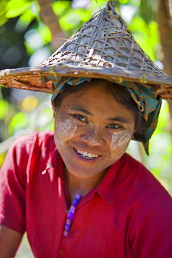 MYA1409 Myanmar, Burma, Rakhine State, Laung Shein. A girl from Laung Shein village wearing a wide-brimmed bamboo hat. Her face is decorated with Thanakha, a local sun cream and skin lotion.