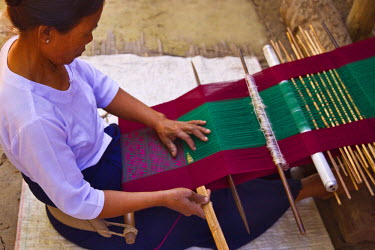 MYA1412 Myanmar, Burma, Rakhine State, Laung Shein. A woman at Laung Shein village weaves brightly coloured cloth at a loom beside her house. Almost every family at Laung Shein has a loom.