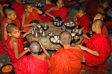 MYA1420 Myanmar, Burma, Rakhine State, Sittwe. Young novice monks eat their main meal at Pathain Monastery where 210 monks live. All their food is donated daily by the community.