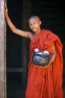 MYA1423 Myanmar, Burma, Rakhine State, Sittwe. A young novice monk with his food bowl and utensils at the Pathain Monastery. All his food is donated daily by the community.