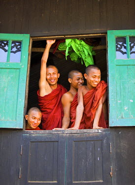 MYA1425 Myanmar, Burma, Rakhine State, Sittwe. Cheerful novice monks look out of their dormitory window at the Pathain Monastery. Most early learning takes place in monastery schools.