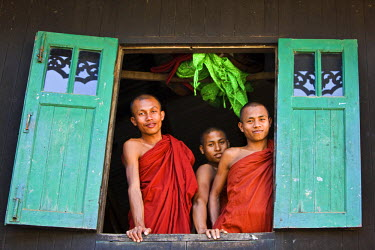MYA1426 Myanmar, Burma, Rakhine State, Sittwe. Three novice monks look out of their dormitory window at the Pathain Monastery. Most early learning takes place in monastery schools.