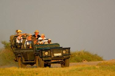 AF05_POX0214_M Tourists watching lions. Okavango Delta. BOTSWANA. Southern Africa.