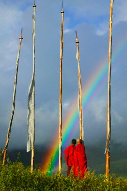 AS04_KSU0067_M Bhutan, Gangtey village, Rainbow over two monks with praying flags in the Phobjikha Valley (MR)