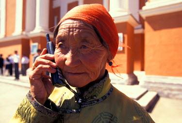 AS25_KSU0032_M Mongolia, Ulan Batar, Mongolian woman using cellular phone on street,  (MR)