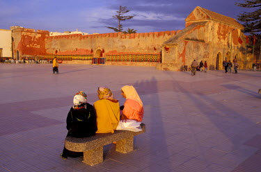 AF29_JME0060_M Morocco, Essaouira (formerly Mogador), Muslim women in traditional dress chatting on bench in town square