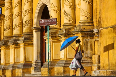 NI01224 Nicaragua, Leon, Woman with blue umbrella walking to Iglesia De La Recoleccion