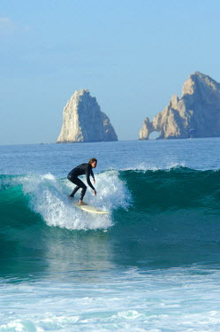 SA13_CMI0365_M Mexico, Baja California Sur, Cabo San Lucas. Baja surfer Mike Fish in front of famous rock formation Los Arcos (The Arches) aka Land's End
