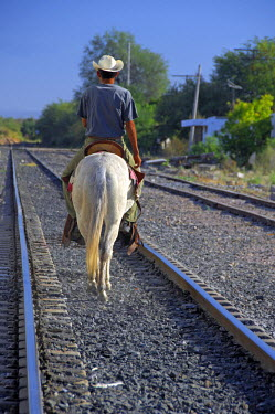 SA13_CMI0994_M Mexico, State of Sinaloa, Copper Canyon. Train station at El Fuerte, everyday life along tracks. Local man on white mule.