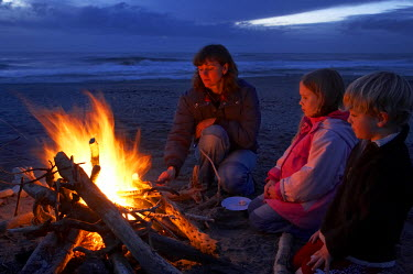 AU02_DWA4255_M Family Toasting Marshmellows on the Beach, Hokitika, West Coast, South Island, New Zealand