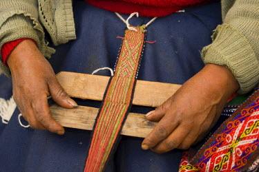 SA17_JME0075_M Hands weaving on traditional foot loom, Cuzco, Peru, South America.
