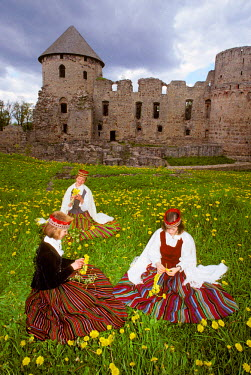EU39_JMI0214_M Three women dressed in traditonal clothes picking dandelions in front of a castle at Cesis, Latvia.