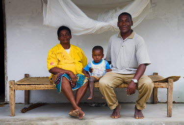 MOZ1337 Mozambique. A family sit together on a hand-made bench