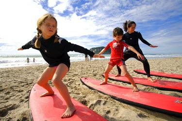 NZ8812 New Zealand, North Island, Coromandel Peninsula. Family surf lesson at Whangamata with Ricky Parker of Whangamata Surf School. (MR)