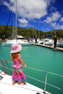 SEY1017 Seychelles, Praslin. Young girl at the railings of a charter yacht leaving the anchorage at Praslin. (MR)