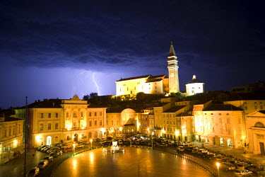 SLO1028 Slovenia, Piran. A night-time view of lightning striking beyond St George Cathedral in the town of Piran; Tartini Square floodlit in the foreground.