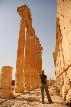 SY1271 Syria, Palmyra. A tourist stands beneath the towering columns of the Bel Temple.(MR)