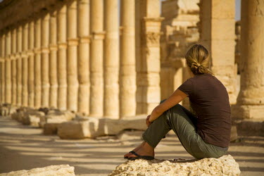 SY1283 Syria, Palmyra. A tourist sits amongst the ancient ruins of Queen Zenobia's city at Palmyra.(MR)