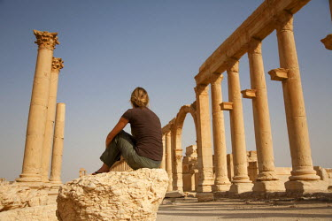SY1284 Syria, Palmyra. A tourist sits amongst the ancient ruins of Queen Zenobia's city at Palmyra.(MR)