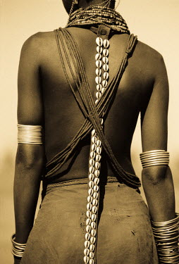 ETH2406 Ethiopia, Omo Delta.  A young Dassanech girl wears a leather skirt, metal bracelets and amulets and beadss. A leather strap with cowrie shells hangs down her back.
