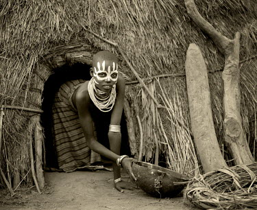 ETH2414 Ethiopia, Omo Delta.  A young Karo girl holds a calabash in the doorway of her hut in the village of Duss.