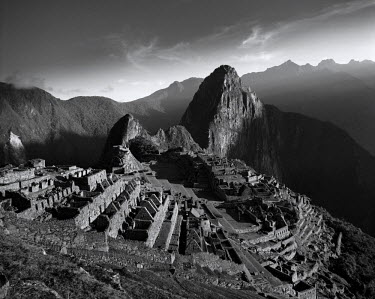 Peru, Urubamba Valley. The first rays of sunlight catch the ancient Inca citadel of Machu Picchu at dawn.