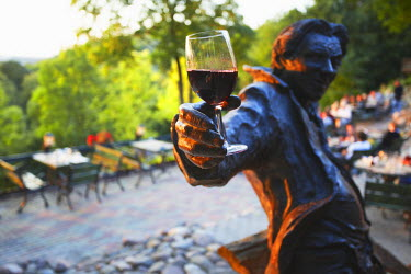 LIT1134AW Lithuania, Vilnius, Uzupis District, Statue Holding Glass Of Red Wine At Outdoor Patio At Tores Restaurant