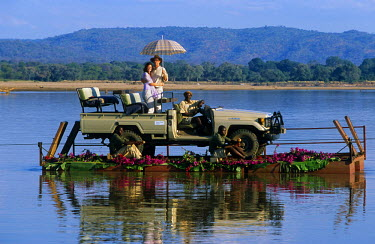 ZAM3113 Zambia, South Luangwa National Park.  A couple on a Robin Pope Safari are pulled across the Luangwa River on a pontoon.
