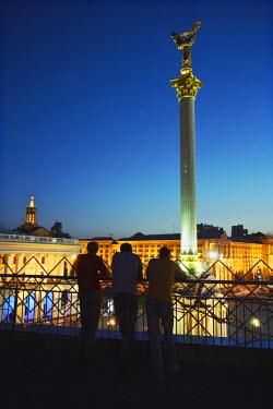 UKR1096AW Men looking at Independence Square (Maydan Nezalezhnosti) at dusk, Kiev, Ukraine