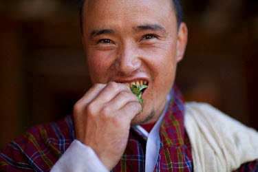 A Bhutanese man in a Gho eating Betel nut in Bhutan