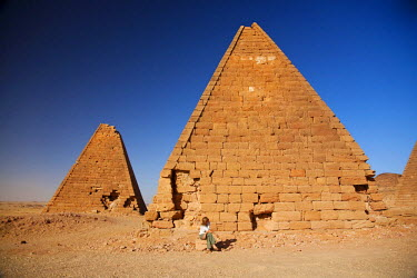 SUD1151 Sudan, Karima. A tourist sits at the base of an ancient pyramid at Karima.