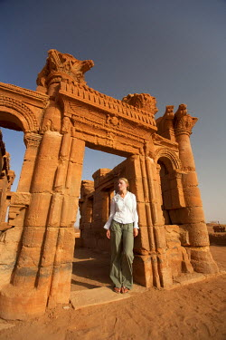 SUD1162 Sudan, Nagaa. A tourist stands in the doorway of a Roman temple ruin at Nagaa.