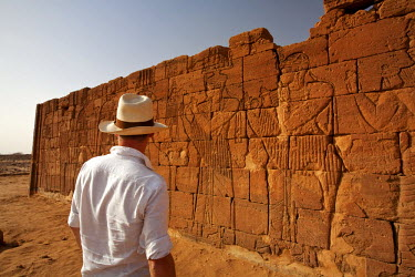 SUD1165 Sudan, Nagaa. A tourist gazes at the hieroglyphics on the Lion Temple at Nagaa.